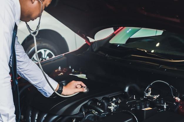 Азиатский человек, держащий стетоскоп осмотр автомобиля резиновые шины автомобиля. закройте руку
