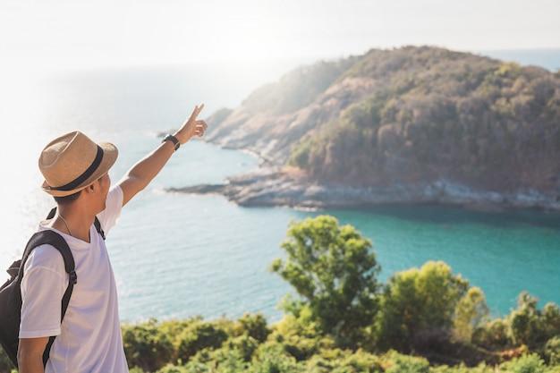帽子をかぶった男は彼の手を幸せにしています。男のアジア人の観光客山と海を見て日没の前に。