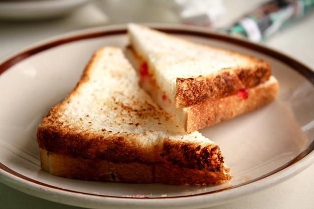 皿にイチゴジャムのスライストーストパンの選択フォーカス