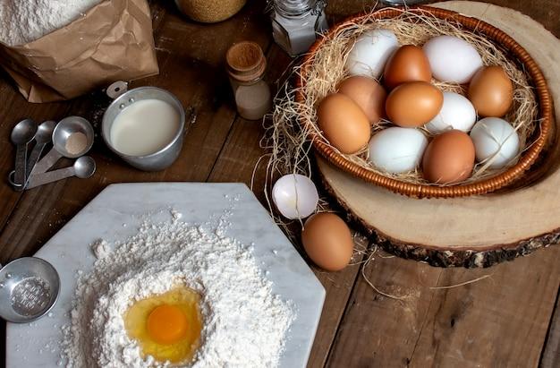 卵、パン生地のオブジェクトのためのスプラットの背景と木製のテーブルに生地と小麦粉