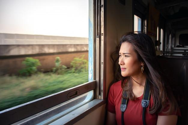 アジアの女性が電車で旅行する
