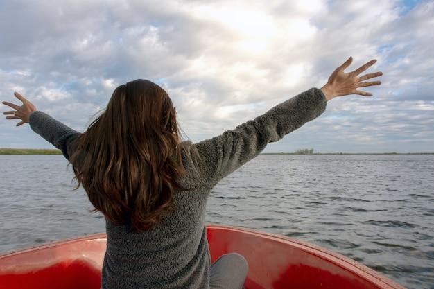 腕を拡張し、ボートで楽しむラグーンに楽しみにしている若い女性の背面図