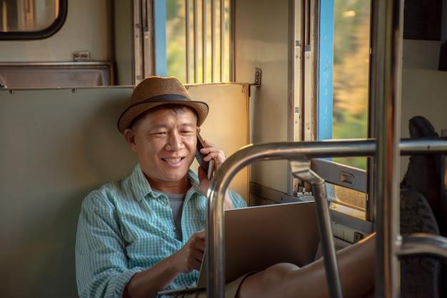 ノートパソコンと携帯電話をオンラインで作業するアジア系のビジネスマンが電車で旅行中にリラックスした気分