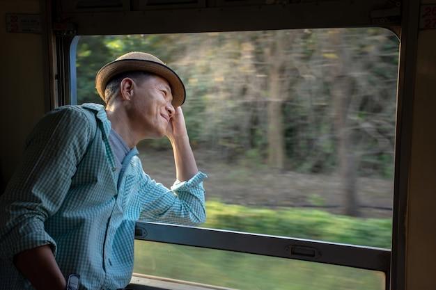 陽気なアジアの乗客が電車の窓の外を見て帽子をかぶっています。