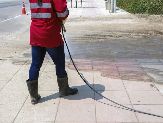 Работник моет пол бетонного блока струей воды высокого давления