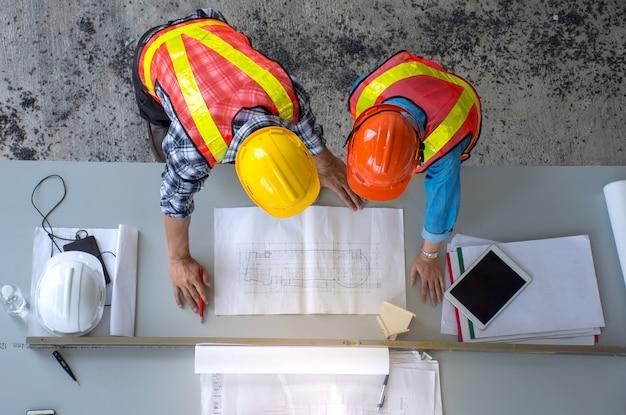 エンジニアリングチームのグループのトップビューは、コンストラクションで建設作業を計画しています