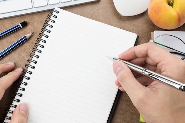男は空白のノートブックページに何かを書くつもりです。
