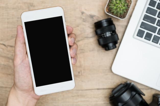 手は写真家のテーブルの上に空白のモックアップ画面を持つスマートフォンを持っています。