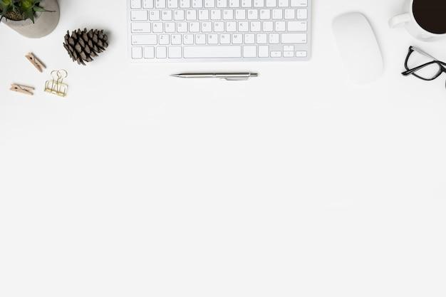 コンピューターのガジェット、一杯のコーヒー、事務用品のモダンな白い事務机テーブル