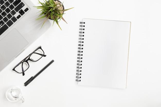 空白のノートブックは、ホワイトオフィスのテーブルの上にあります。平面図、平面レイアウト。