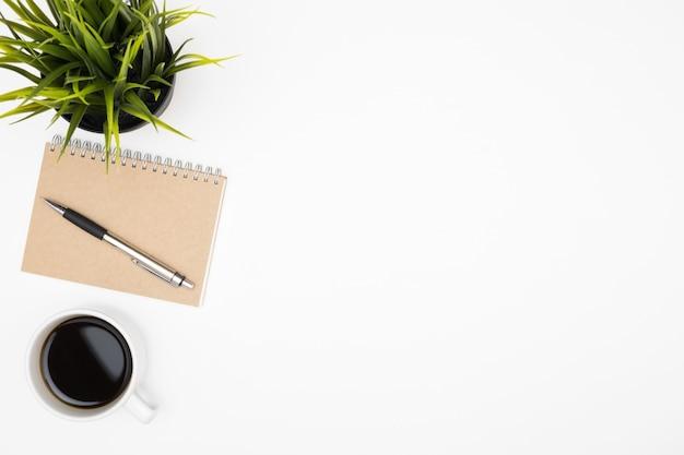 一杯のコーヒーとペンとノートとホワイトオフィスデスクテーブル。