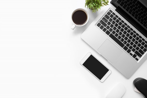 スマートフォン、ラップトップコンピューター、コーヒーのカップと消耗品の白いオフィスデスクテーブル。