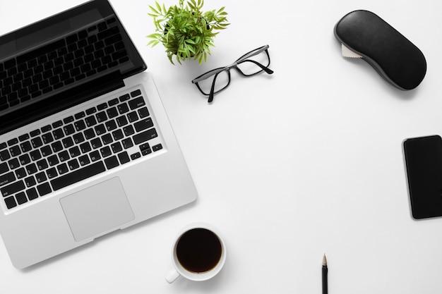 ラップトップコンピューター、コーヒーのカップと事務用品の白い事務机テーブル。
