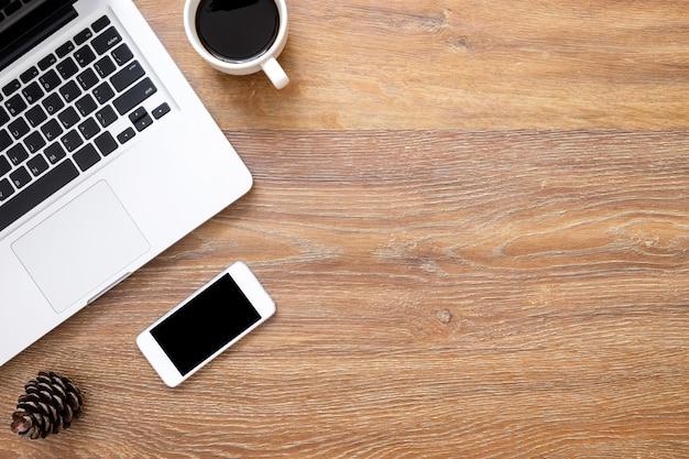 スマートフォン、ノートパソコン、一杯のコーヒーと木製のオフィスデスクテーブル。