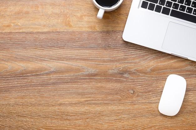 ノートパソコン、一杯のコーヒーとワイヤレスマウスの木製オフィスデスクテーブル。
