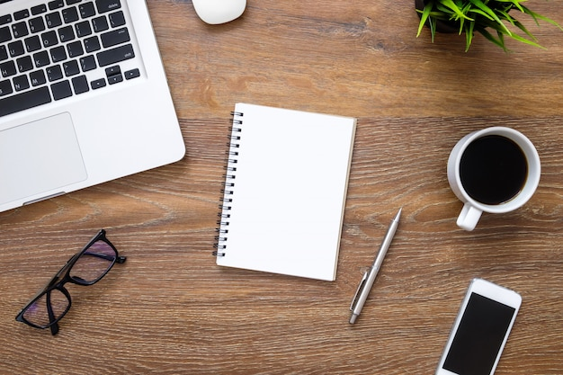 空白のノートブック、コンピューターガジェットおよび消耗品の木製オフィスデスクテーブル。