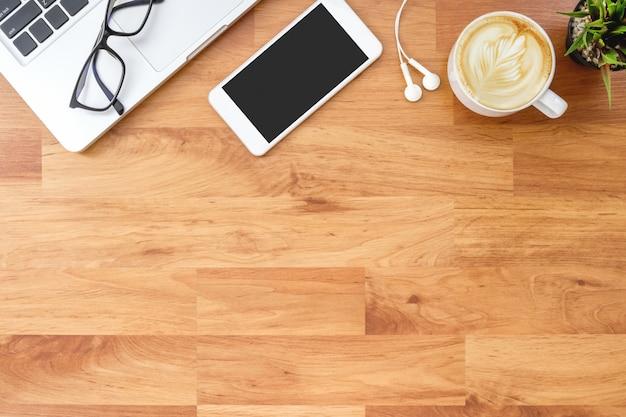 ラップトップコンピューター、スマートフォン、消耗品の木製オフィスデスクテーブル。