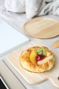 ミックスフルーツパイの皿がベッドの上にあります。ベッドのコンセプトで朝食します。
