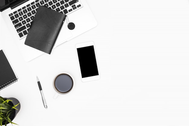 ノートパソコン、スマートフォン、一杯のコーヒーと消耗品の白いオフィスデスクテーブル。
