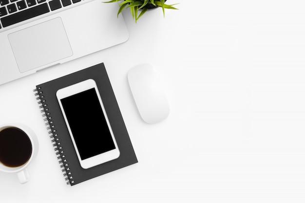 空白の画面を持つスマートフォンは、ノートパソコンと消耗品の白いオフィスデスクテーブルの上です。