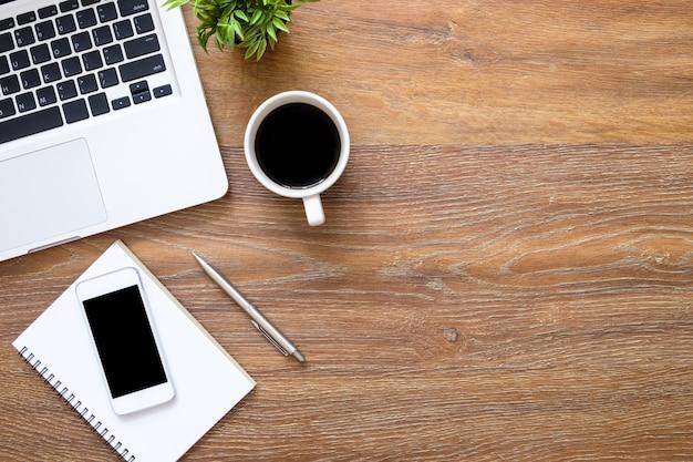 スマートフォン、ラップトップコンピューターおよび消耗品の木製オフィスデスクテーブル。