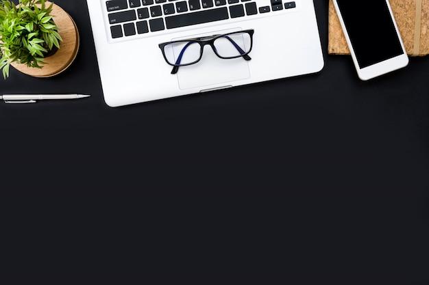 ノートパソコン、スマートフォン用品と黒のオフィスデスクテーブル。平面図、平面レイアウト。