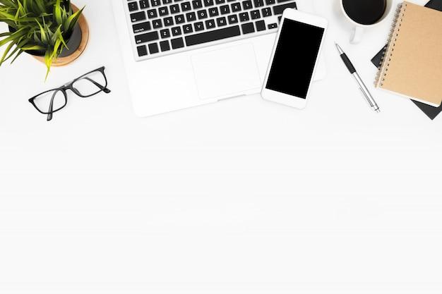 ノートパソコン、スマートフォン、事務用品の白い事務机テーブル。
