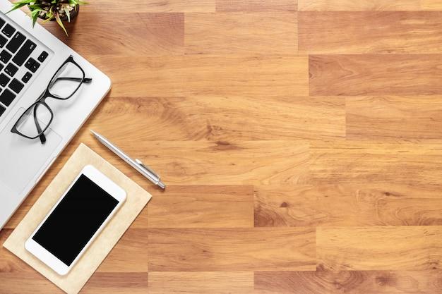 ノートパソコン、スマートフォン、および消耗品の木製オフィスデスクテーブル。