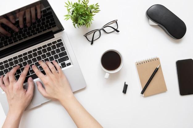 一杯のコーヒーと事務用品の白いオフィスデスクテーブルの上のラップトップコンピューターで入力する男。