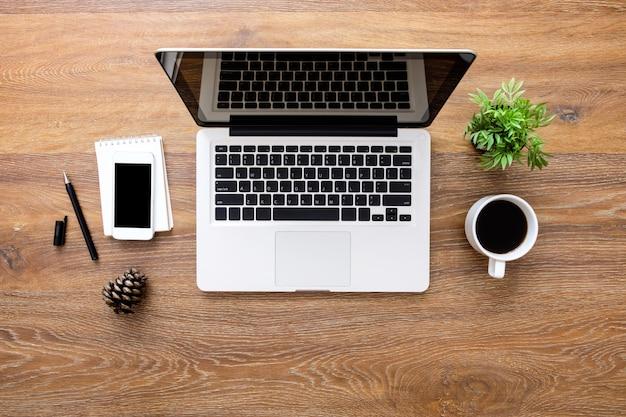 ラップトップコンピューター、スマートフォン、一杯のコーヒーと消耗品の木製オフィスデスクテーブル。平面図、平面レイアウト。