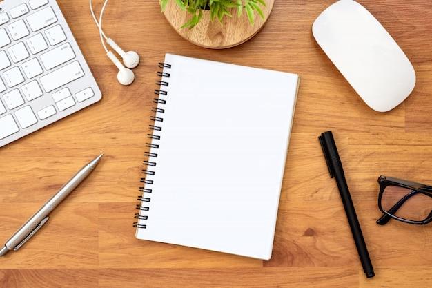 空白のノートブックは、供給と木製のオフィスデスクテーブルの上にあります。平面図、平面レイアウト。