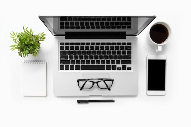 ラップトップコンピューター、スマートフォン、一杯のコーヒー、ノート、消耗品の白い事務机テーブル。平面図、平面レイアウト。