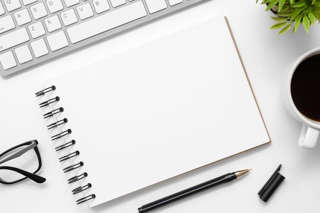 空白のノートブックは、供給とモダンな白いオフィスデスクテーブルの上です。コピースペース平面図、平面レイアウト。