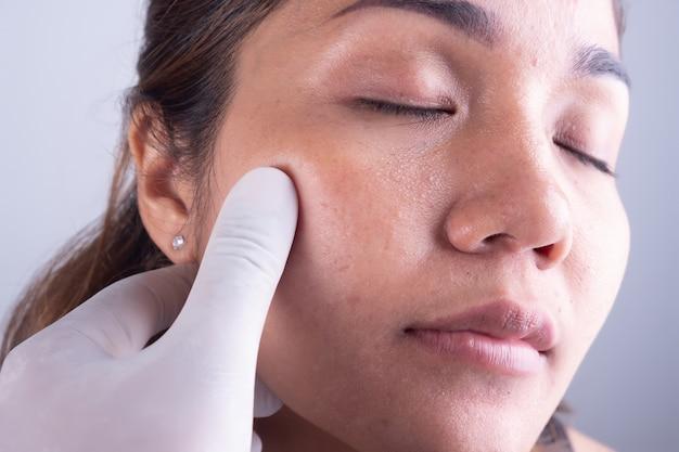 アジアの女性の顔と医師の手