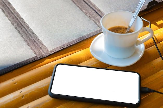 朝のコーヒーカップと太陽電池で竹製のテーブルの上に携帯電話を置く
