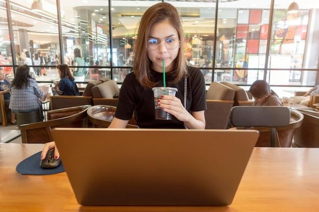 コンピュータのラップトップでコーヒーショップで働く美しい女性