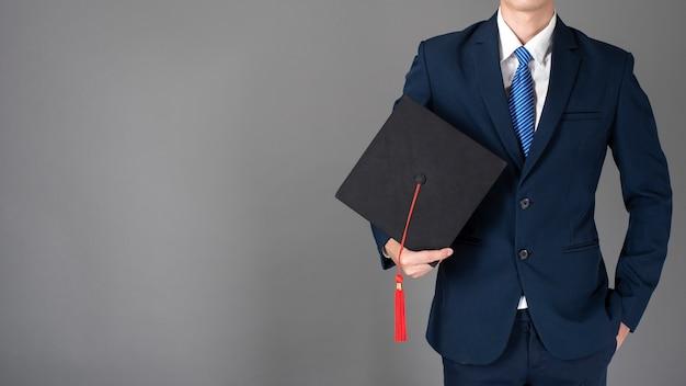Деловой человек проводит выпускной шляпе, концепция бизнес-образования