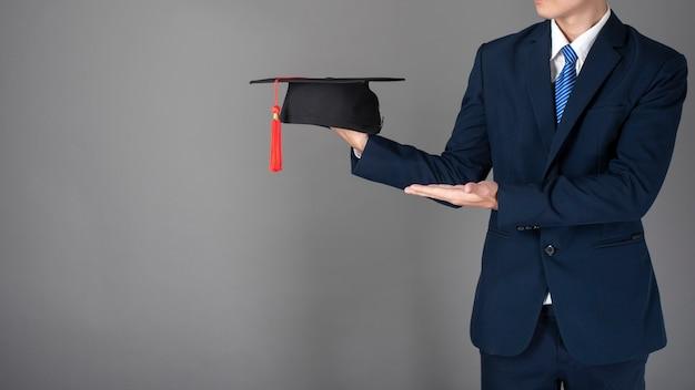 ビジネスマンは、卒業帽子、ビジネス教育の概念を保持している