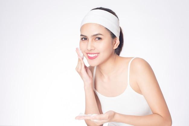 美しい女性は白い背景に彼女の顔を洗っている