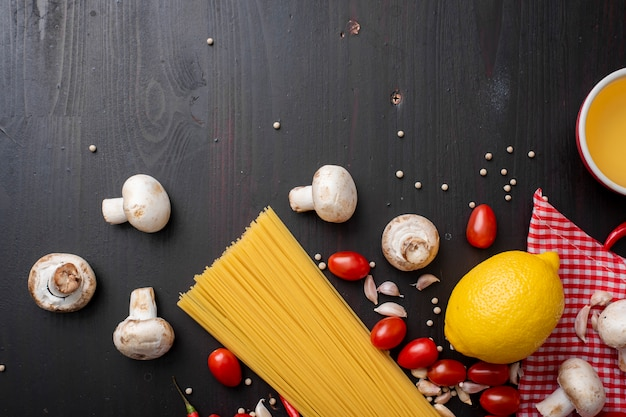 黒い木製の机の上にスパゲッティの材料、トップビュー。