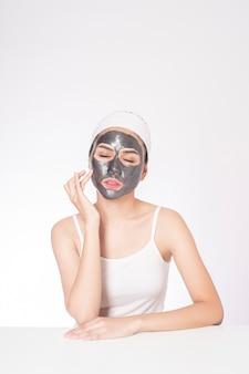 白い背景に彼女の顔をマスキングする美しい女性
