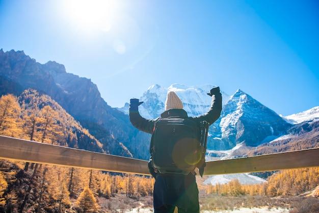 秋の雪山でハイキングをする男成功、人々がコンセプトを旅行する