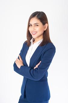 青いスーツの美しいビジネス女性は白い背景の上笑顔します。