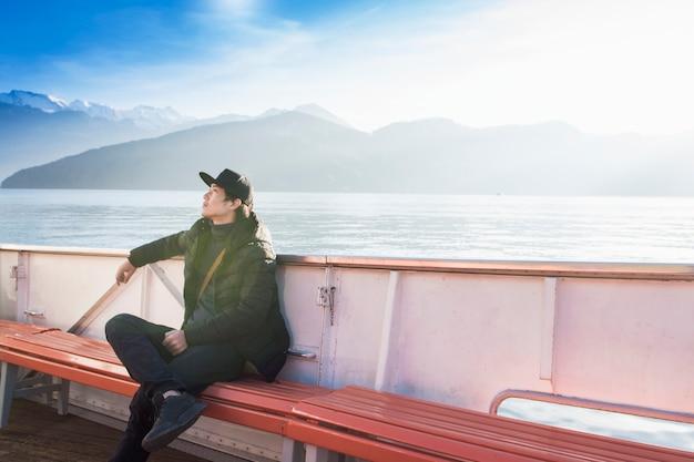 ハンサムな男は山とボートに座っています。