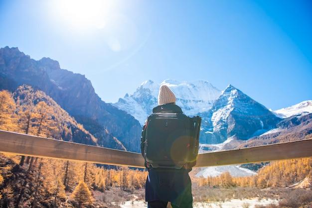 秋の雪のピーク山でのハイキング、人旅行の概念