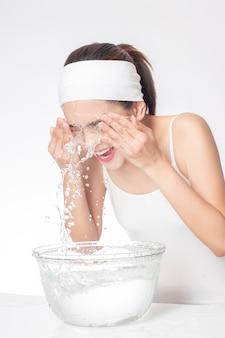 美しい女性は白い背景の上の彼女の顔を洗っています。