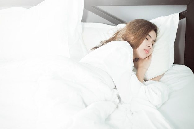 Красивая женщина спит на кровати