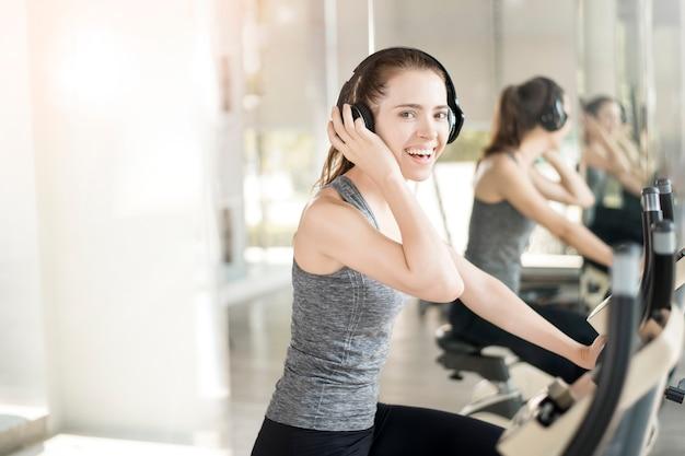 かなり若いスポーツ女性はジム、健康的なライフスタイルで自転車で運動します。