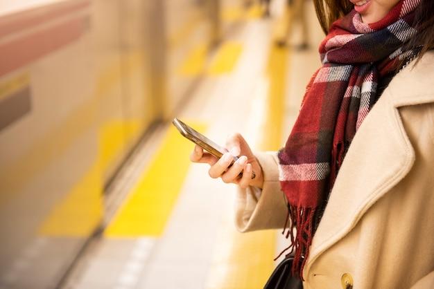 クローズアップ女性がスマートフォンを遊んでいます。