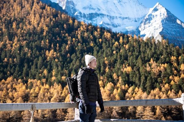 ハイキング男、秋の雪のピーク山で楽しんでいます
